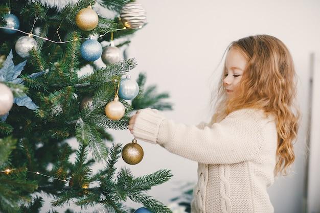 Маленькая блондинка девочка помогает украсить