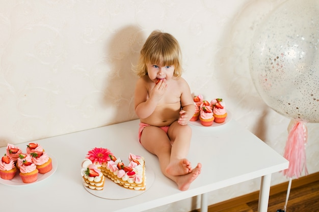 Little blonde baby girl in pink pants sitting on the white table near her birthday cake and different pink sweets