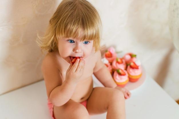 Маленькая блондинка двухлетняя девочка в розовых штанах сидит на белом столе рядом со своим праздничным тортом и разными розовыми сладостями на столе
