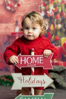 Little blonde baby girl with christmas signboards