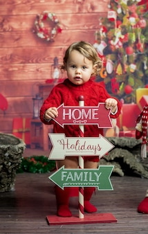 Little blonde baby girl with christmas signboards.