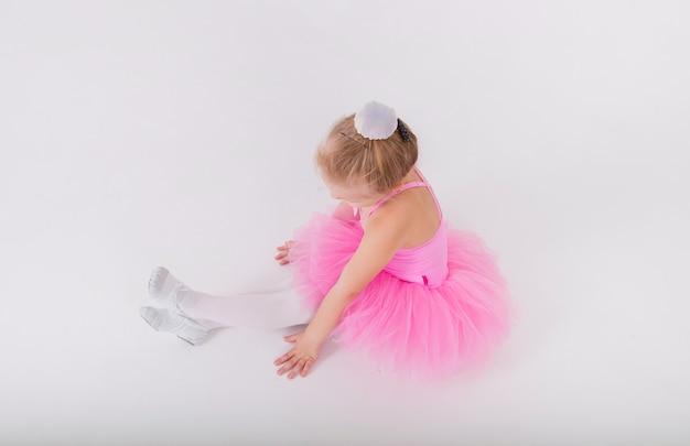 핑크 투투 드레스에 작은 금발 발레리나는 흰 벽에 앉아