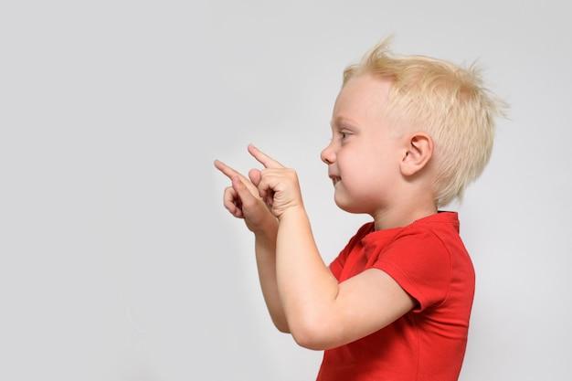 赤いtシャツを着た小さな金髪の少年が彼の指を指しています。テキスト用のスペース。広告のための場所。白色の背景