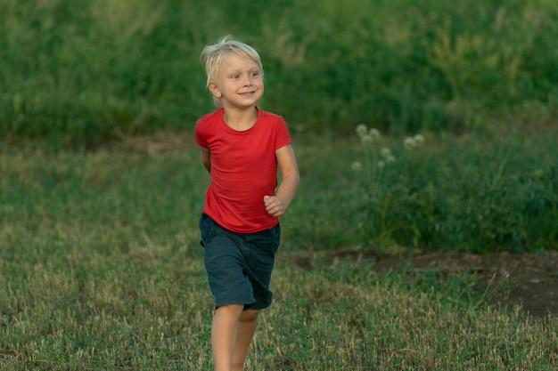Маленький белокурый мальчик в красной футболке гуляет по зеленому полю