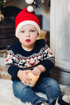 Little blonde boy playing with christmas presents and boxes.