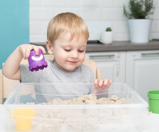 운동 모래 집에서 놀고 작은 금발 소년.
