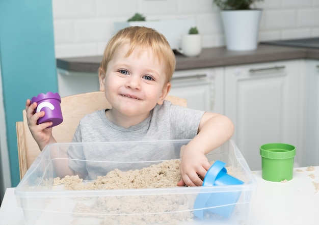 Little blonde boy playing with kinetic sand at home.