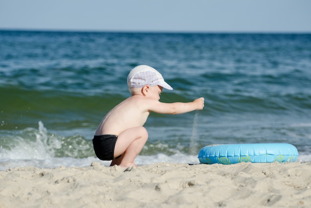 Little blonde boy playing with sand on the seashore