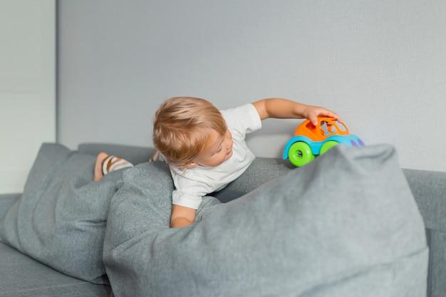 어린 금발 소년은 회색 소파에서 장난감 자동차를 가지고 노는다