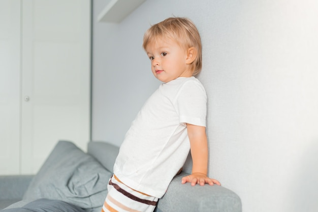 Little blonde boy plays with a toy car on a gray sofa