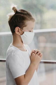 祈る小さな金髪の少年
