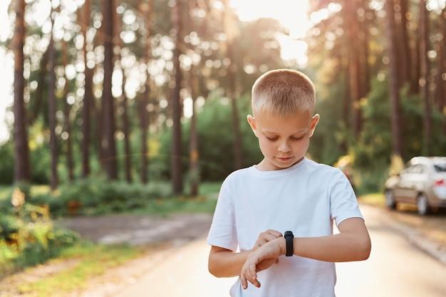 피트니스 벤드 터치 버튼과 터치 스크린을 사용하는 작은 금발 소년은 공원에서 야외 포즈를 취하고 버튼을 터치하고 도로에서 실행하기 전에 스마트 시계를 설정합니다.