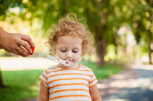 Little blonde curly girl blowing soap bubbles in summer park