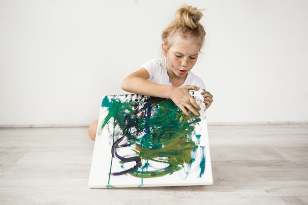 Little blonde female child with hairbn and freckles wearing white t-shirt occupied with her picture. cute, adorable girl sitting on a floor with colourful canvas on her knees.