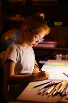 Little blonde girl 7 years old seating at the white table with warm lamp and making he school homework at dark night time