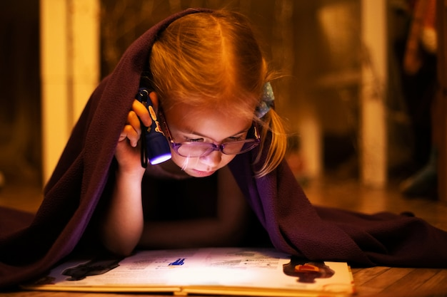 Little blonde girl 7 years old with glasses reading the book under the blanket with little flashlight at dark night time