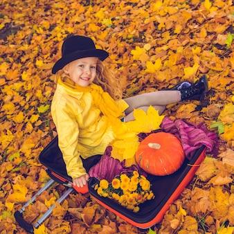 Little blonde girl and big pumpkin in autumn