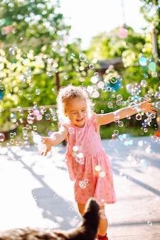 Маленькая белокурая девушка ловя мыльные пузыри. счастливое детство, концепция летнего отдыха.