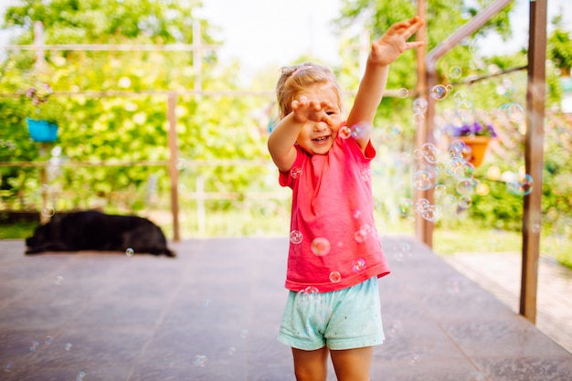 Little blonde girl catching a soap bubbles. happy childhood, summer holiday concept.