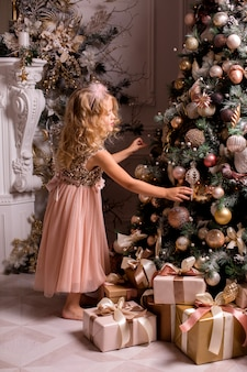 Little blonde girl decorates christmas tree in beautiful interior