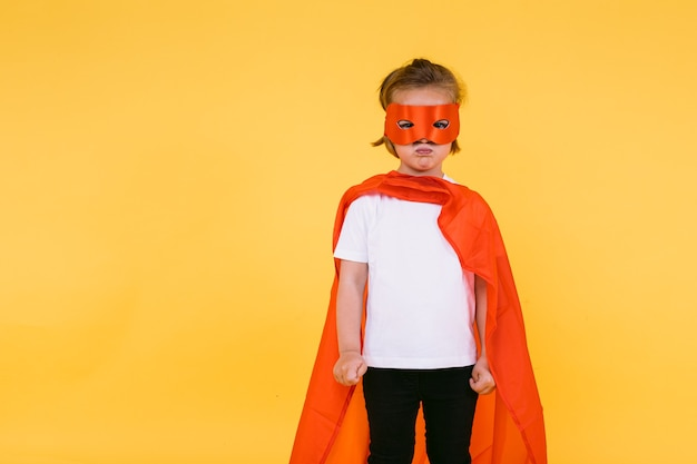 Little blonde girl dressed as a superheroine superhero with a cape and red mask, angry, with the cape to the side, on yellow background