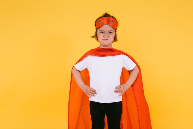 Little blonde girl dressed as a superheroine superhero with a cape and red mask, angry, with her arms akimbo serious, on yellow background