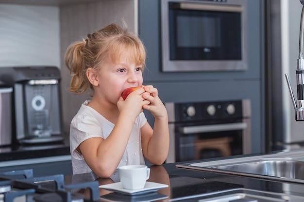 台所でリンゴを食べる小さなブロンドの女の子