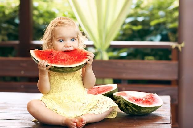 Little blonde girl eating a juicy watermelon in the garden. children eat fruit on the street. healthy food for children. toddler gardening.