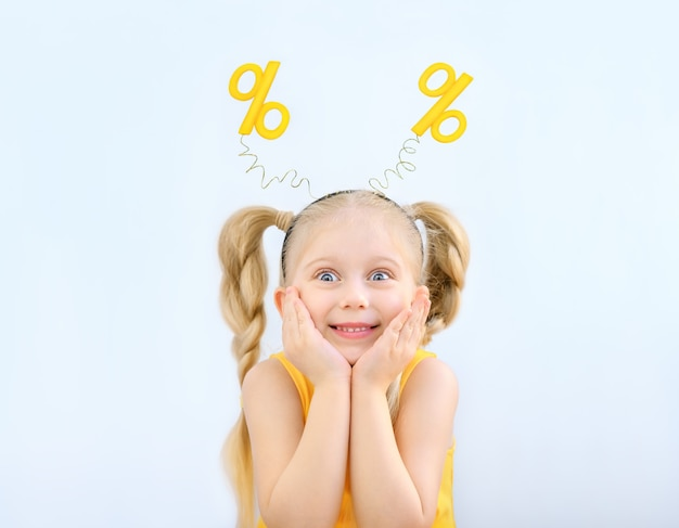 Little blonde girl funny portrait in a headband with yellow percents on it