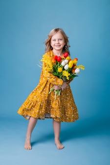 Маленькая блондинка держит букет тюльпанов на синем фоне в студии
