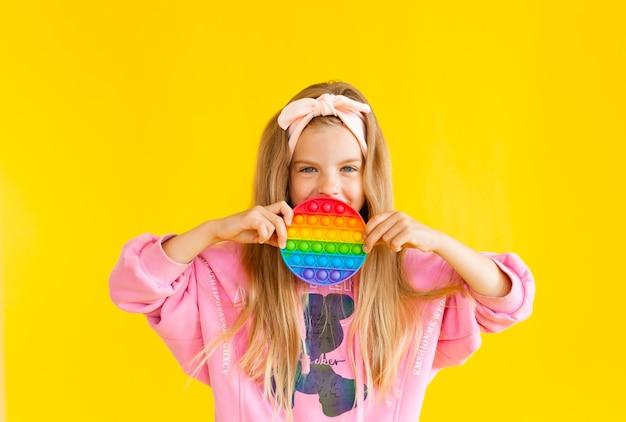 Маленькая блондинка держит игрушку-антистресс pop it на желтом фоне с местом для текста