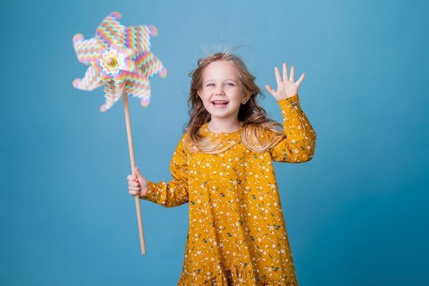 Маленькая блондинка держит в руках детскую мельницу