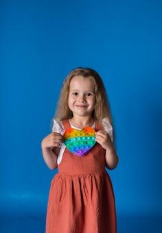 Маленькая блондинка держит обучающую игрушку-антистресс на синей поверхности с местом для текста