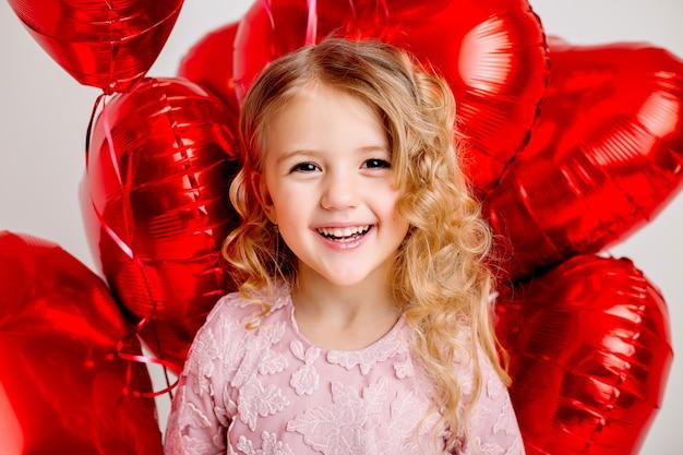 핑크 드레스에 금발 소녀 웃 고 흰 벽 발렌타인 개념에 붉은 심장 모양의 풍선을 많이 들고