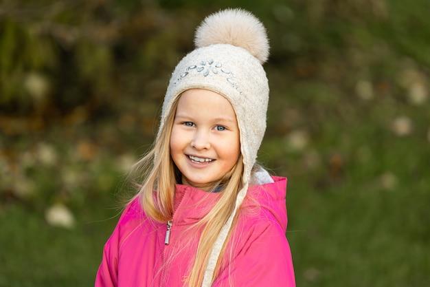 가을 공원에서 분홍색 재킷을 입은 금발 소녀