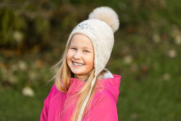 秋の公園でピンクのジャケットを着た小さなブロンドの女の子