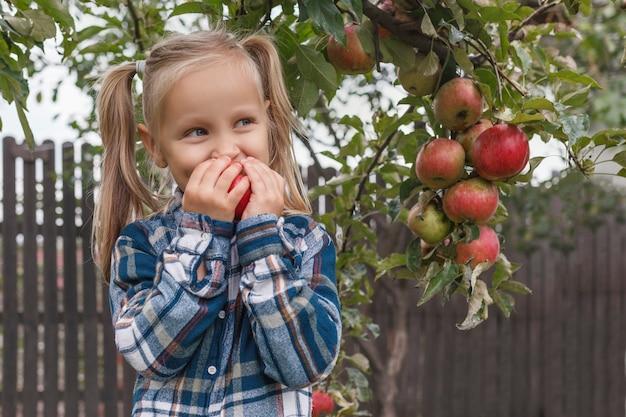 격자 무늬 셔츠를 입은 어린 금발 소녀는 정원에서 사과를 양손으로 들고 먹는다