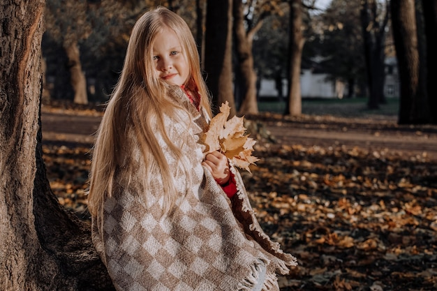 秋の公園で格子縞の鞭で小さなブロンドの女の子