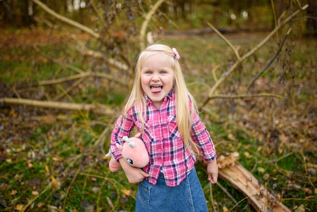Маленькая белокурая девушка в шортах рубашки и джинсовой ткани гуляет в парк осени. девушка показывает язык. крупный план.