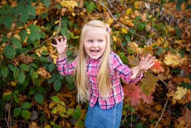 Маленькая белокурая девушка в шортах рубашки и джинсовой ткани гуляет в парк осени.