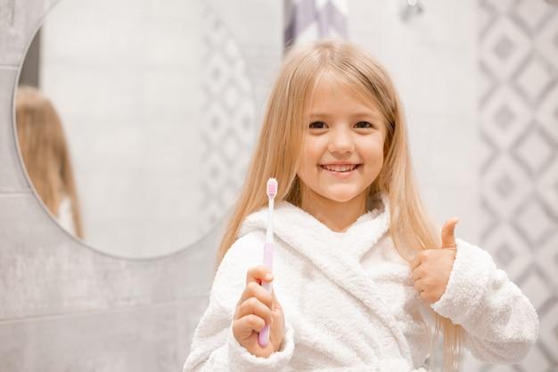 하얀 목욕 가운을 입은 금발 소녀가 욕실 거울 앞에서 이를 닦는다