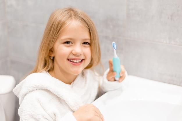 白いバスローブを着た小さなブロンドの女の子は、前に電動歯ブラシで歯を磨きます