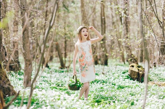 白いドレスを着た金髪少女は、春の森を歩きます。彼女の頭に帽子とスノードロップのバスケットを持つかわいい女の子の肖像画。