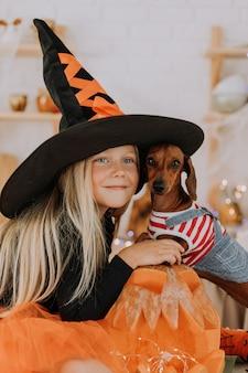巨大な魔女の帽子とオレンジ色のふくらんでいるスカートの魔女の衣装を着た小さなブロンドの女の子は犬を抱きます