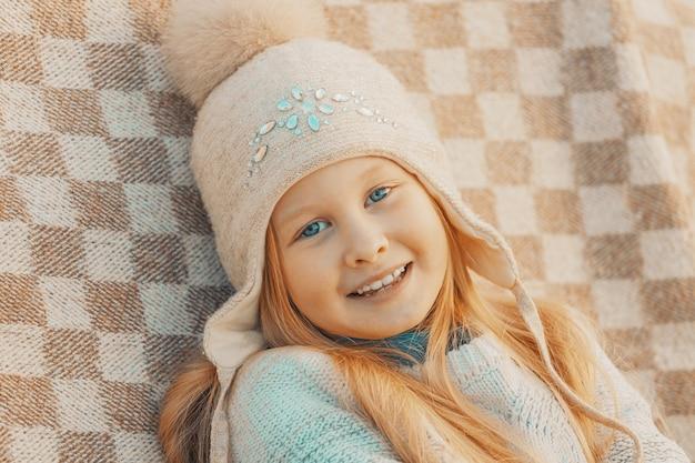 公園の格子縞のウールの帽子をかぶった小さなブロンドの女の子