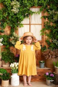 黄色のドレスで金髪少女は笑顔し、麦わら帽子にしがみつきます。子供の頃の概念。園芸。春の庭で美しい子供の肖像画。子供たちは屋外で遊ぶ。春のコンセプト、自然