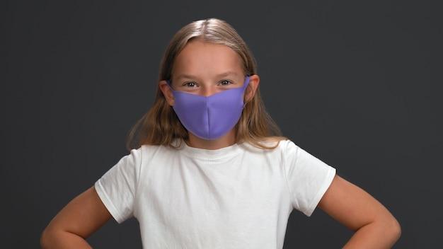 薄紫色のマスクの小さなブロンドの女の子は微笑む。探している白人の子供