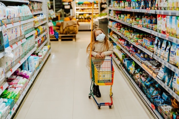 スーパーマーケットの棚の近くにトロリーと医療マスクの小さなブロンドの女の子