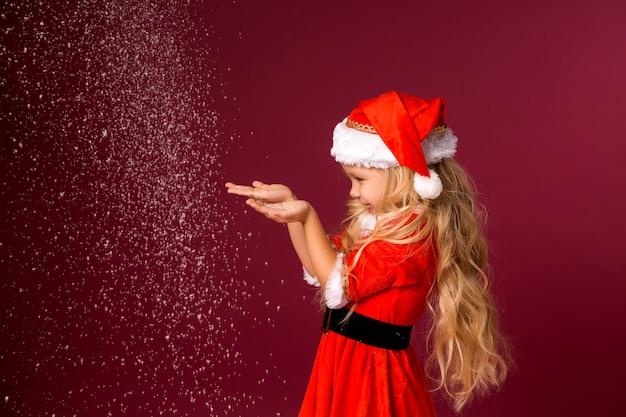 Маленькая блондинка в костюме санты ловит снег