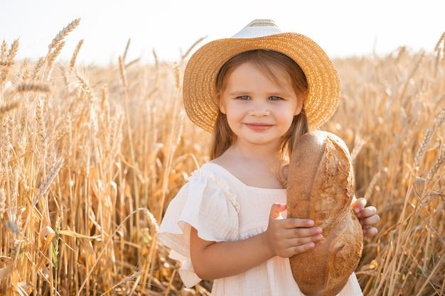 Маленькая блондинка в соломенной шляпе и бежевом муслиновом платье держит хлеб на пшеничном поле на закате